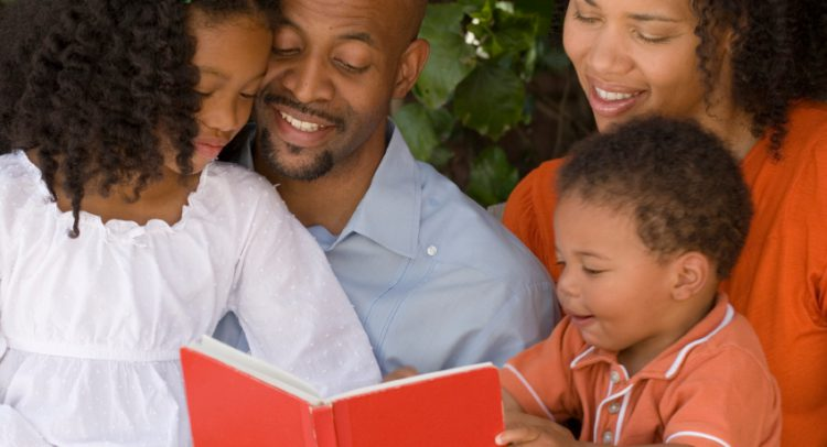 Parents read a book to children.